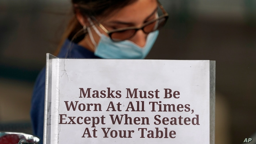 Hostess Carla Alexander waits behind a sign that ask customers to wear masks at the Saint Arnold Brewing Company, Friday, June…