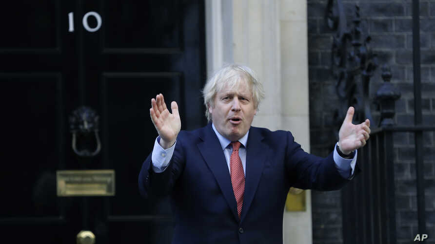 """Britain's Prime Minister Boris Johnson applauds on the doorstep of 10 Downing Street in London during the weekly """"Clap for our…"""