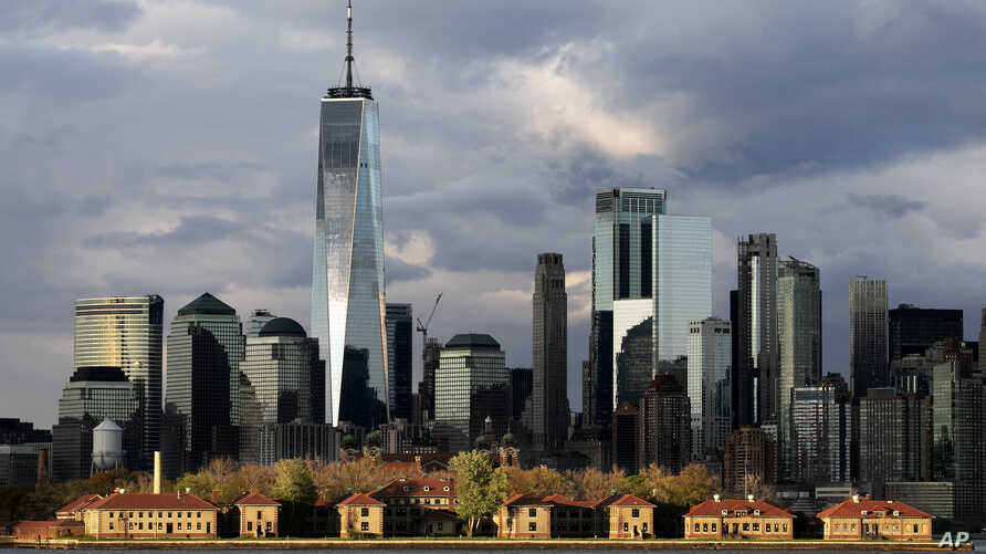 Buildings on Ellis Island in New York Harbor stand in front of the New York skyline, Monday, May 11, 2020. (AP Photo/Mark…