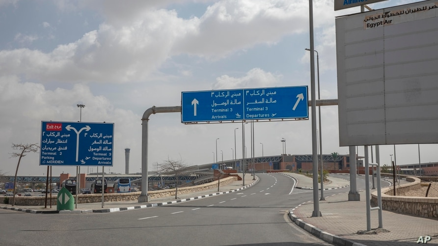 This March 19, 2020 photo, shows an empty road leading to departures at the Cairo International Airport during a travel ban due…