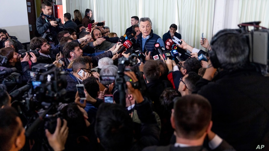 Argentina's President Mauricio Macri talks to journalists after casting his vote during primary elections in Buenos Aires,…