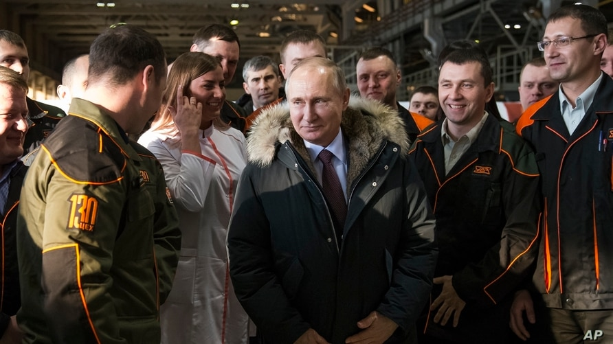 FILE - In this March 6, 2018, file photo, Russian President Vladimir Putin listens to employees of Uralvagonzavod factory in…