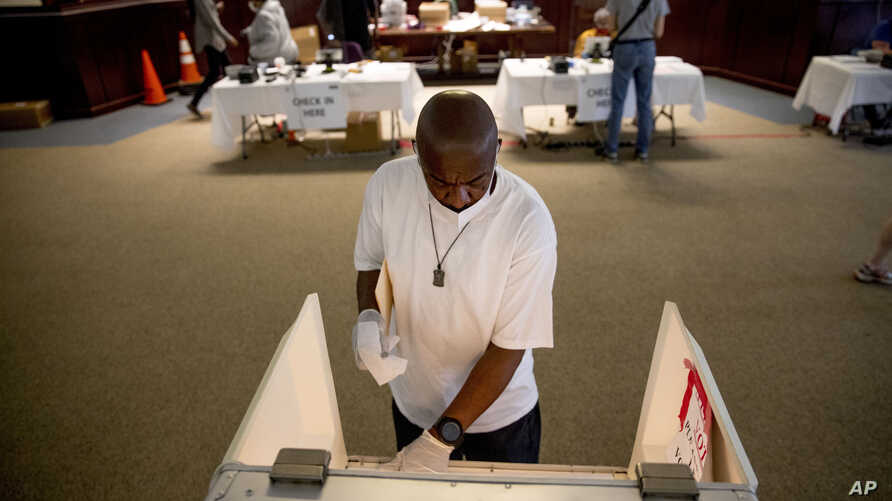 Darren Atkinson wears a mask as he wipes down a voting booth at a voting center during primary voting in Washington, Tuesday,…