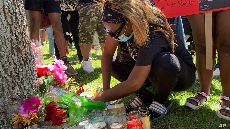 Demonstrators bring candles and flowers, Saturday, June 13, 2020, around a tree where the body of Robert Fuller was found dead…