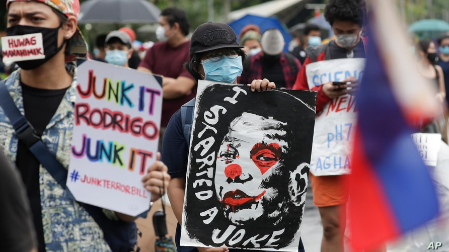 A protester holds a caricature of Philippine President Rodrigo Duterte during an anti-terror bill rally at the University of…