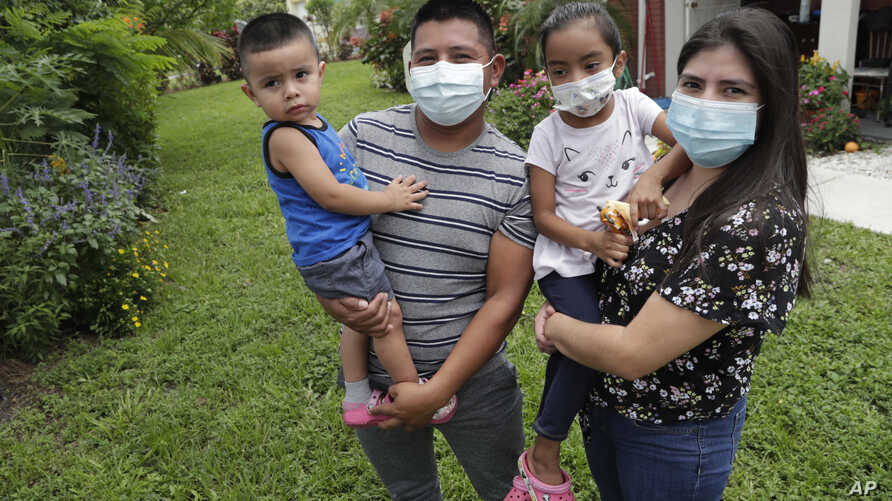 In this Sunday, June 7, 2020, photo, Elbin Sales, second from left, poses for a photograph with his wife, Yecenia Solorzano,…