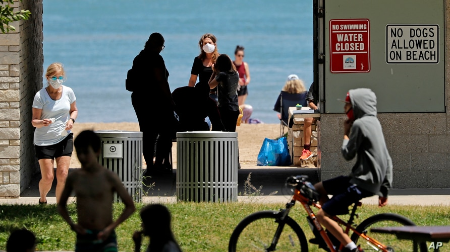 Signs are seen at Clark Street Beach during COVID-19 as people gather in Evanston, Ill., Tuesday, June 23, 2020. Gathering of…