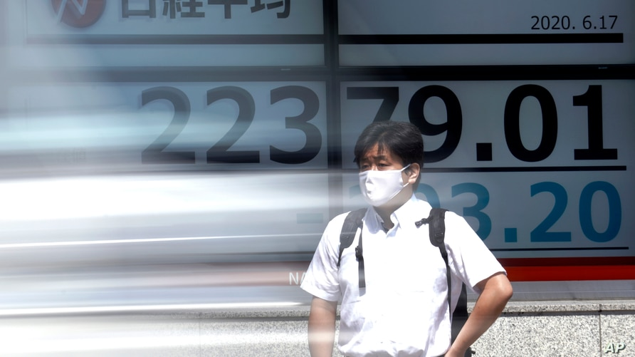 A man stands in front of an electronic stock board showing Japan's Nikkei 225 index at a securities firm as a vehicle goes by…