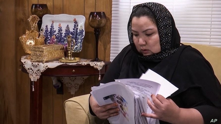 In this image from video, Zumret Dawut, a Uighur from China's far western Xinjiang region, holds documents she brought with her…