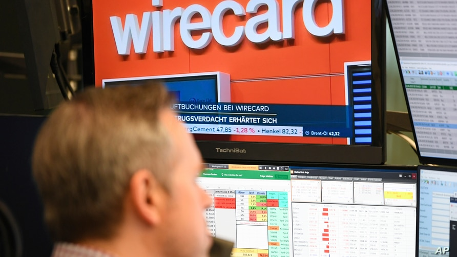 A stockbroker sits in front of a screen with news about the payment service provider Wirecard at the Frankfurt Stock Exchange…