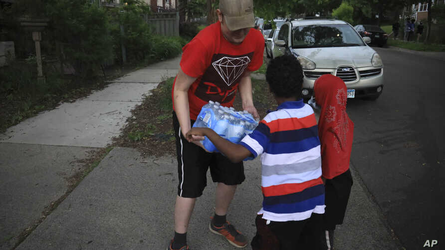 Michael Grunke help his neighbor's children with a case of water during his neighborhood watch activity, which started after…