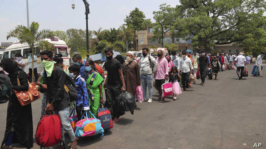 Passengers stand in a queue outside Hyderabad Railway Station to catch a train to return to their home states in Hyderabad,…