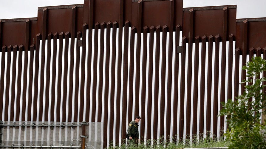 A border patrol agent walks along a border wall separating Tijuana, Mexico, from San Diego, Wednesday, March 18, 2020, in San…