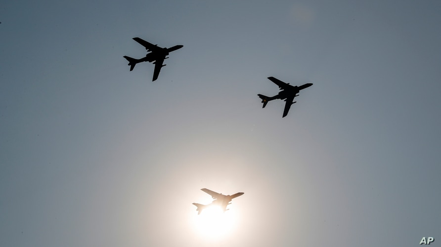 China's H-6 bomber jets fly in formation past the sun during a parade to commemorate the 70th anniversary of the founding of…