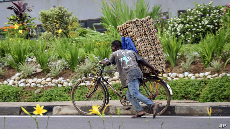 In this photo taken Thursday, March 26, 2020 a man transports cartons of eggs on the back of a bicycle due to restrictions on…