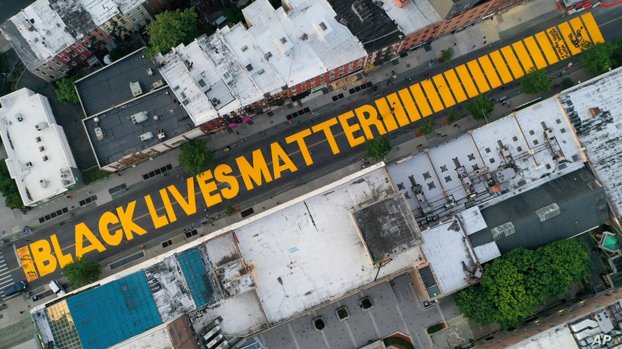 "FILE- In this June 15, 2020, file photo, a sign reading ""Black Lives Matter"" is painted in orange on Fulton Street in the…"