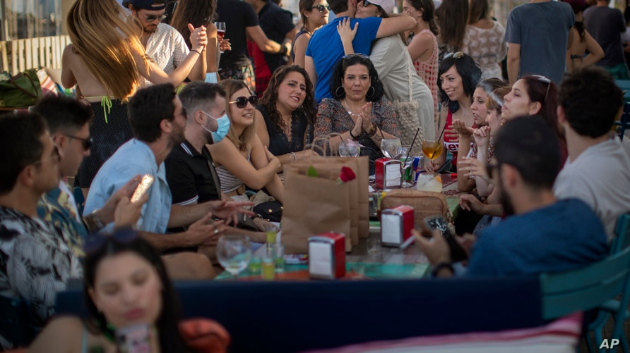 People enjoy in a snack bar in Barcelona, Spain, Sunday, June 21, 2020. Spain ended a national state of emergency after three…