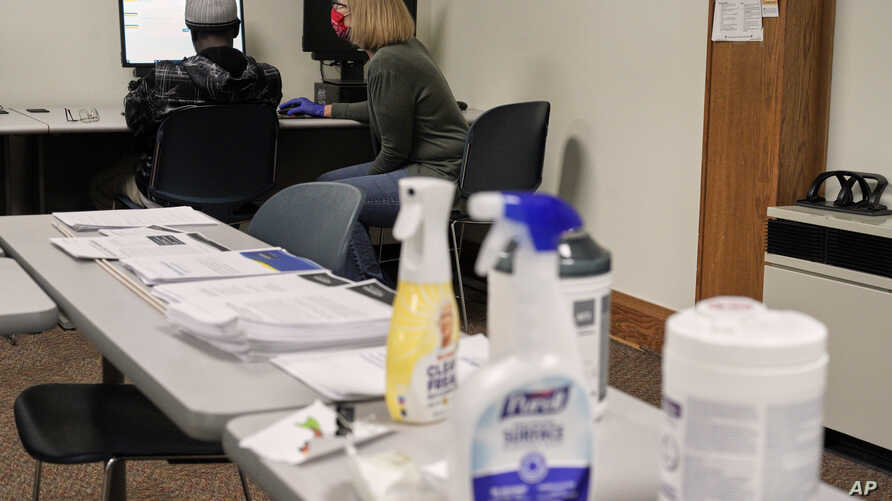 A person seeking employment, left, gets assistance from a staff member at the Nebraska Heartland Workforce Solutions office in…