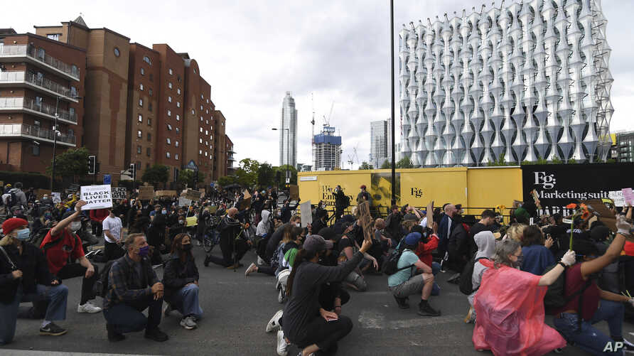 Protesters kneel as they gather in front of the US embassy during the Black Lives Matter protest rally in London, Sunday, June…
