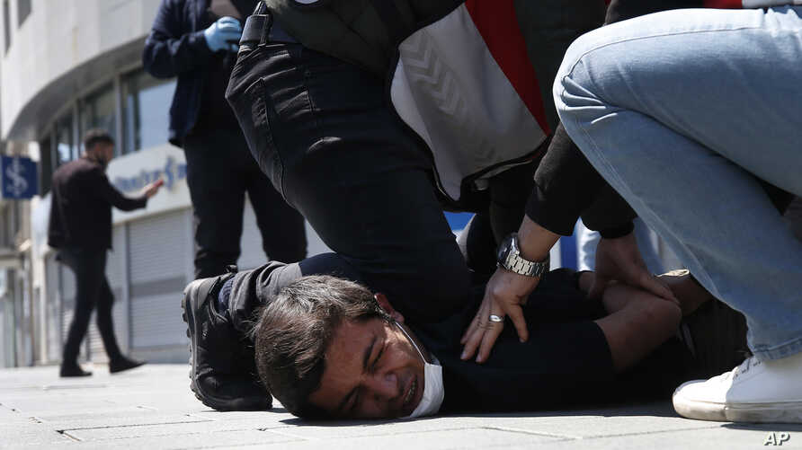 FILE - In this May 1, 2020, file photo, Turkish police officers arrest a demonstrator wearing a face mask for protection…