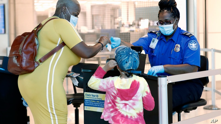 TSA agent Patrisa Johnson assist travelers as they clear security for flights out of Love Field in Dallas, Wednesday, June 24,…