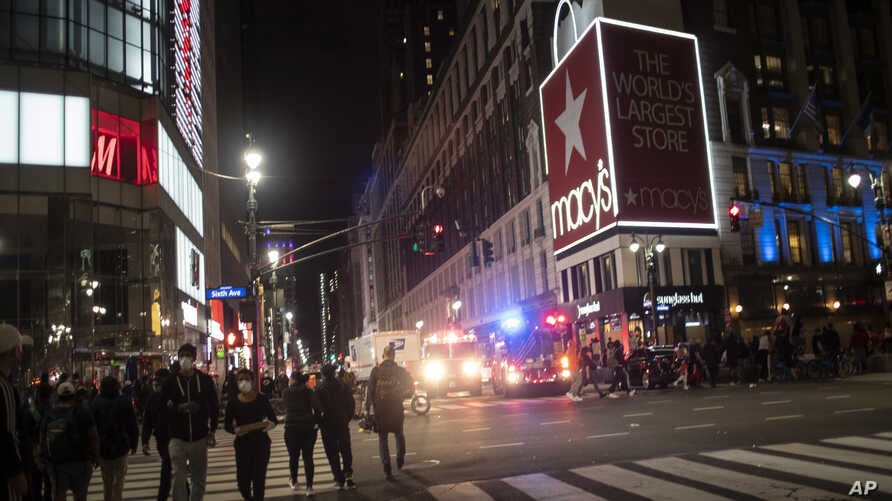 New York police officers park their vehicles outside Macy's store after it was broken into hours after a solidarity rally…
