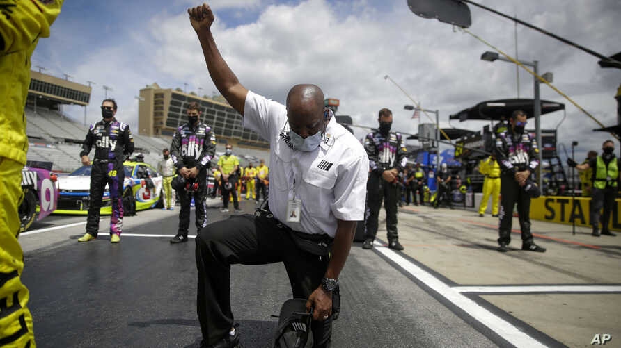 A NASCAR official kneels during the national anthem before a NASCAR Cup Series auto race at Atlanta Motor Speedway on Sunday,…