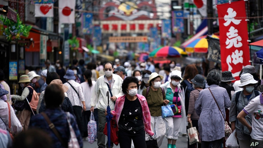 A street is crowded by shoppers in Tokyo Wednesday, June 24, 2020. Japan's economy is opening cautiously, with social…