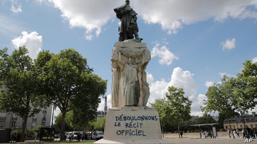 """A graffiti reading """"down with the official version"""" is seen on the basement of the statue of French military commander Joseph…"""