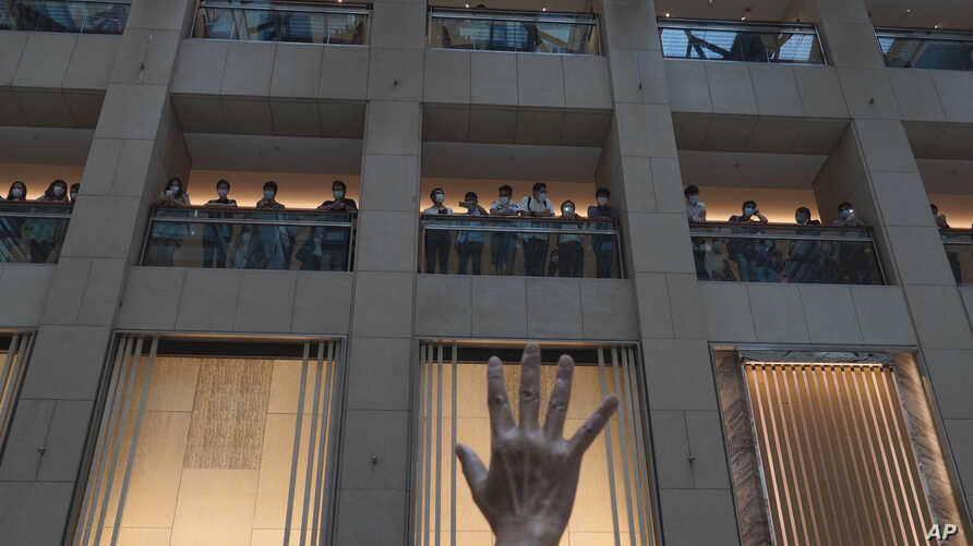 """A protester gestures with five fingers, signifying the """"Five demands - not one less"""" in a shopping mall during a protest…"""