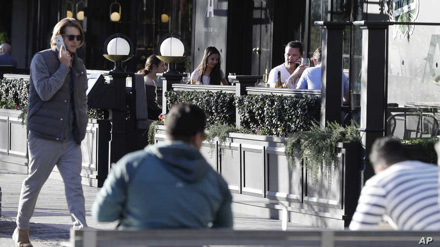People sit in an outdoor restaurant area in Christchurch, New Zealand, Monday, June 8, 2020. New Zealand appears to have…