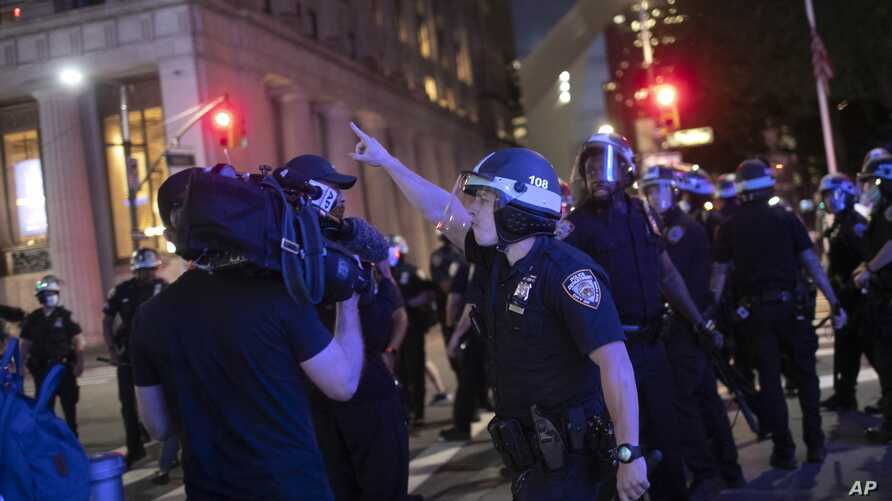 A police officer shouts at Associated Press videojournalist Robert Bumsted, Tuesday, June 2, 2020, in New York. New York City…