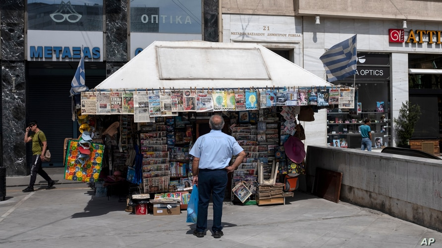 A man checks newspapers' front pages at a kiosk in Athens, on Friday, June 5, 2020. The European Commission says Greece is…