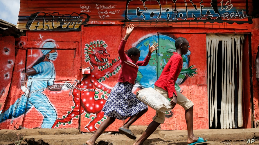 Children run down a street past an informational mural warning people about the dangers of the COVID-19 coronavirus, in the…
