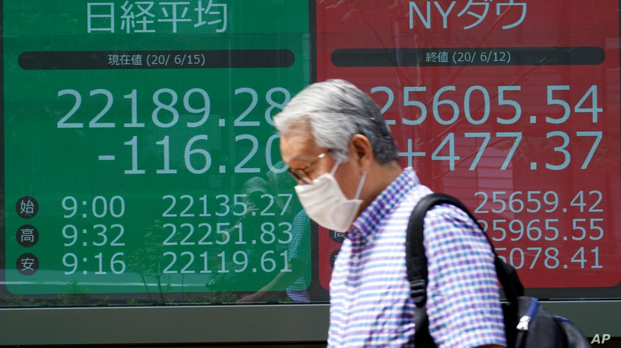 A man walks past an electronic stock board showing Japan's Nikkei 225 index and New York Does index at a securities firm in…
