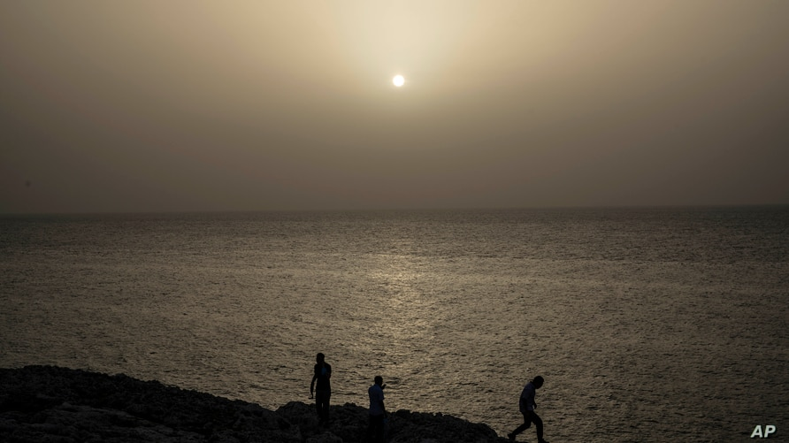 People watch the sunset while a cloud of Sahara dust hangs in the air in Havana on Wednesday, June 24, 2020. The massive cloud…