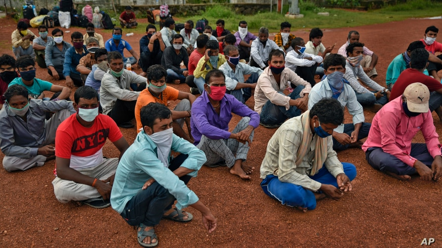 Migrant workers from Bihar state, wearing masks as a precaution against the coronavirus, wait for buses to catch home bound…