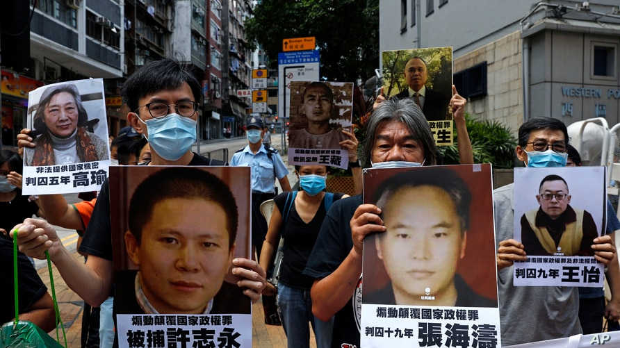 Pro-democracy demonstrators hold up portraits of jailed Chinese civil rights activists, lawyers and legal activists as they…