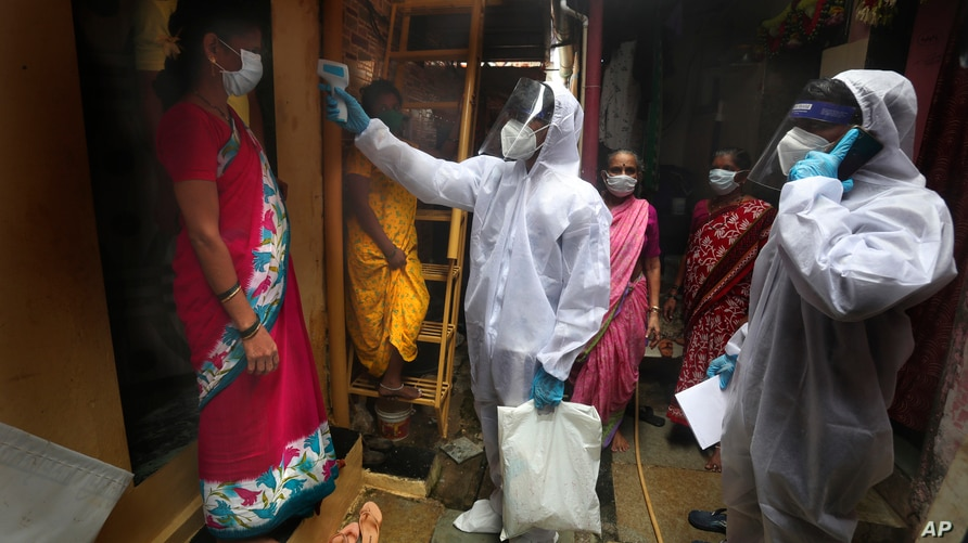 A health worker checks the body temperature of a resident, as others await their turn during a free medical checkup in a slum…