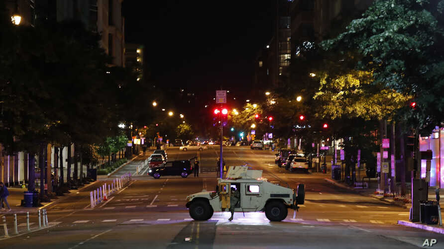 A military Humvee blocks an intersection along K Street in downtown Washington as demonstrators protest