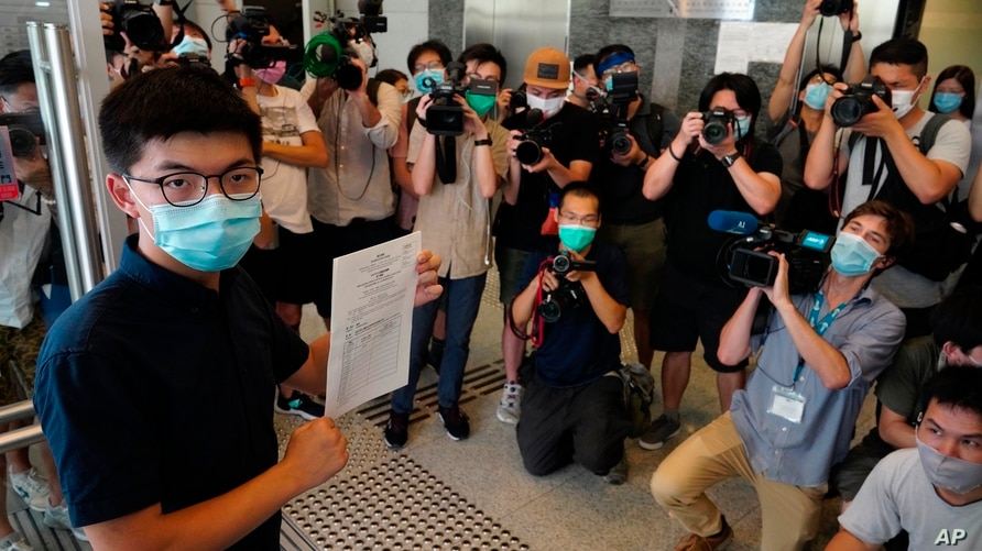 Hong Kong pro-democracy activist Joshua Wong poses for a picture with the nomination papers as he files his candidacy in…