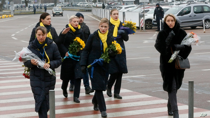 A crew of a Ukrainian airlines carry flowers to pay tribute to the flight crew members of the Ukrainian 737-800 plane that…
