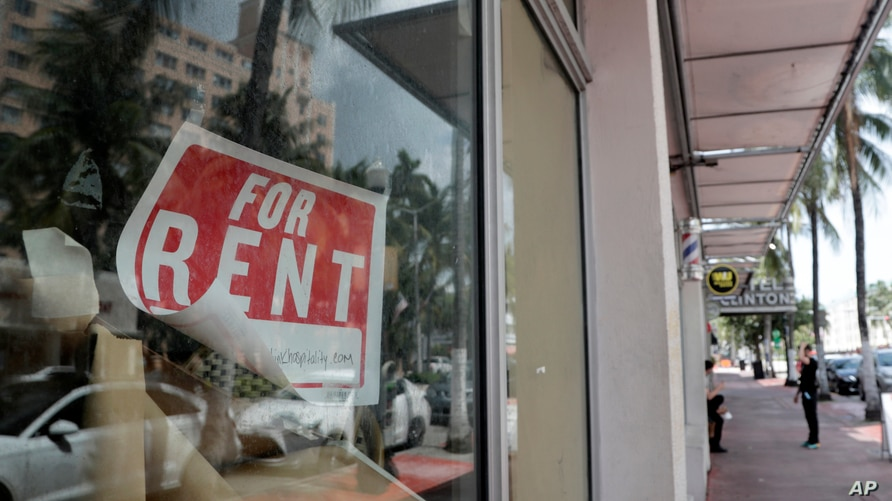 FILE - In this July 13, 2020 file photo, a For Rent sign hangs on a closed shop during the coronavirus pandemic in Miami Beach,…