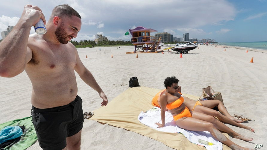 Cameron Baca, left, of Riverside County, California, puts on sunscreen while at Miami Beach, Florida's famed South Beach,…