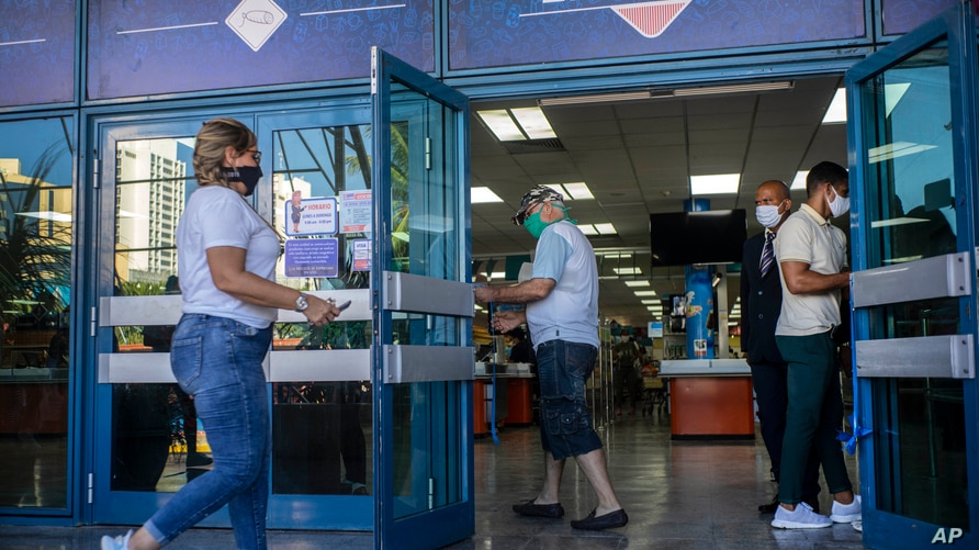 People wearing protective face masks amid the spread of the new coronavirus enter a grocery store that accepts U.S. dollars in…