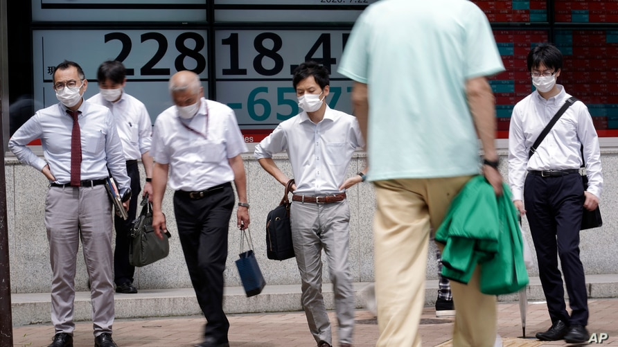 People wearing face masks walk past an electronic stock board showing Japan's Nikkei 225 index at a securities firm in Tokyo…
