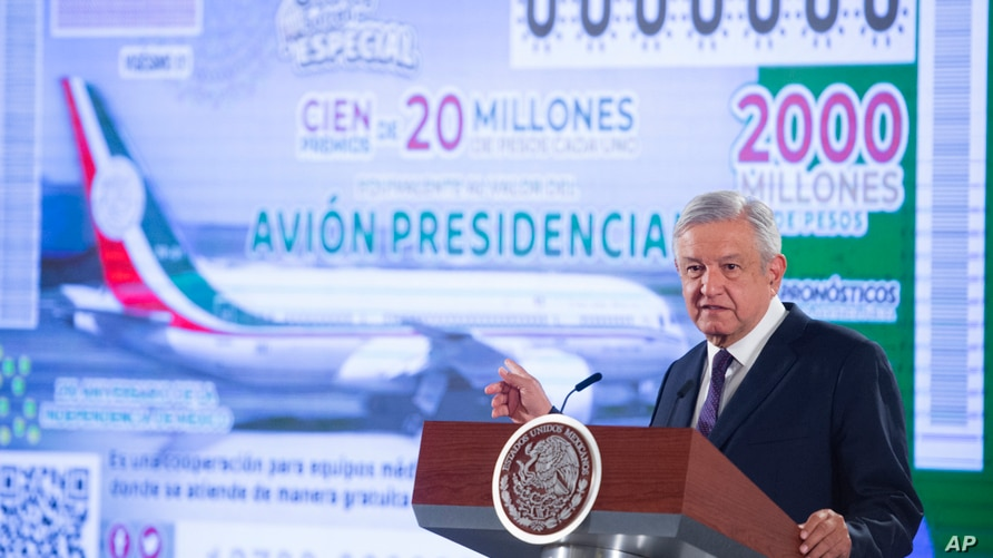 In this photo provided by Mexico's Presidential Press Office, President Andres Manuel Lopez Obrador stands in front of an image…