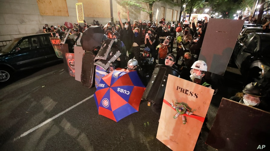 Demonstrators shield themselves from advancing federal officers during a Black Lives Matter protest Tuesday, July 28, 2020, in…