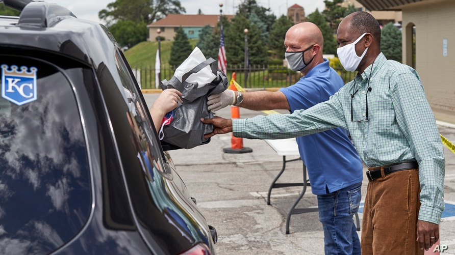 A motorist is handed a bag containing information about open positions at a drive-thru job fair in Omaha, Neb., Wednesday, July…