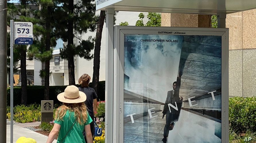 """In this June 27, 2020 photo, people walk by a poster promoting the long-awaited Christopher Nolan film """"Tenet,"""" in Los Angeles…"""